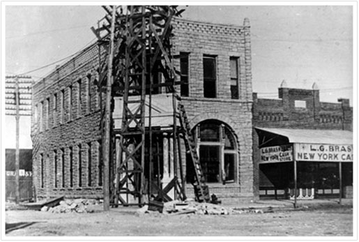 Exterior view of First National Bank building during reconstruction following fire in 1902