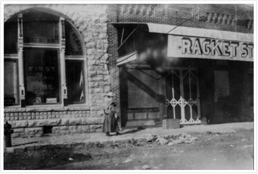 Exterior view of portion of First National Bank building and adjacent 'Racket' Store - early 1900s
